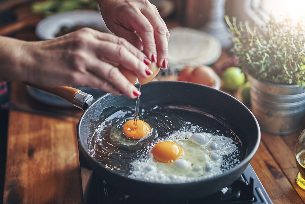 Hands cracking eggs into a skillet while making a keto-friendly breakfast