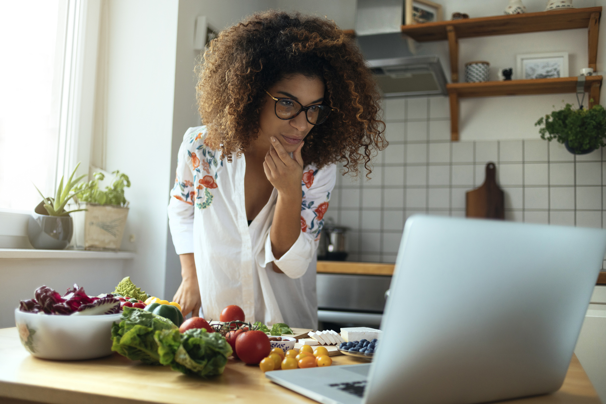 Woman in her kitchen looking at her computer for keto diet recipe ideas.