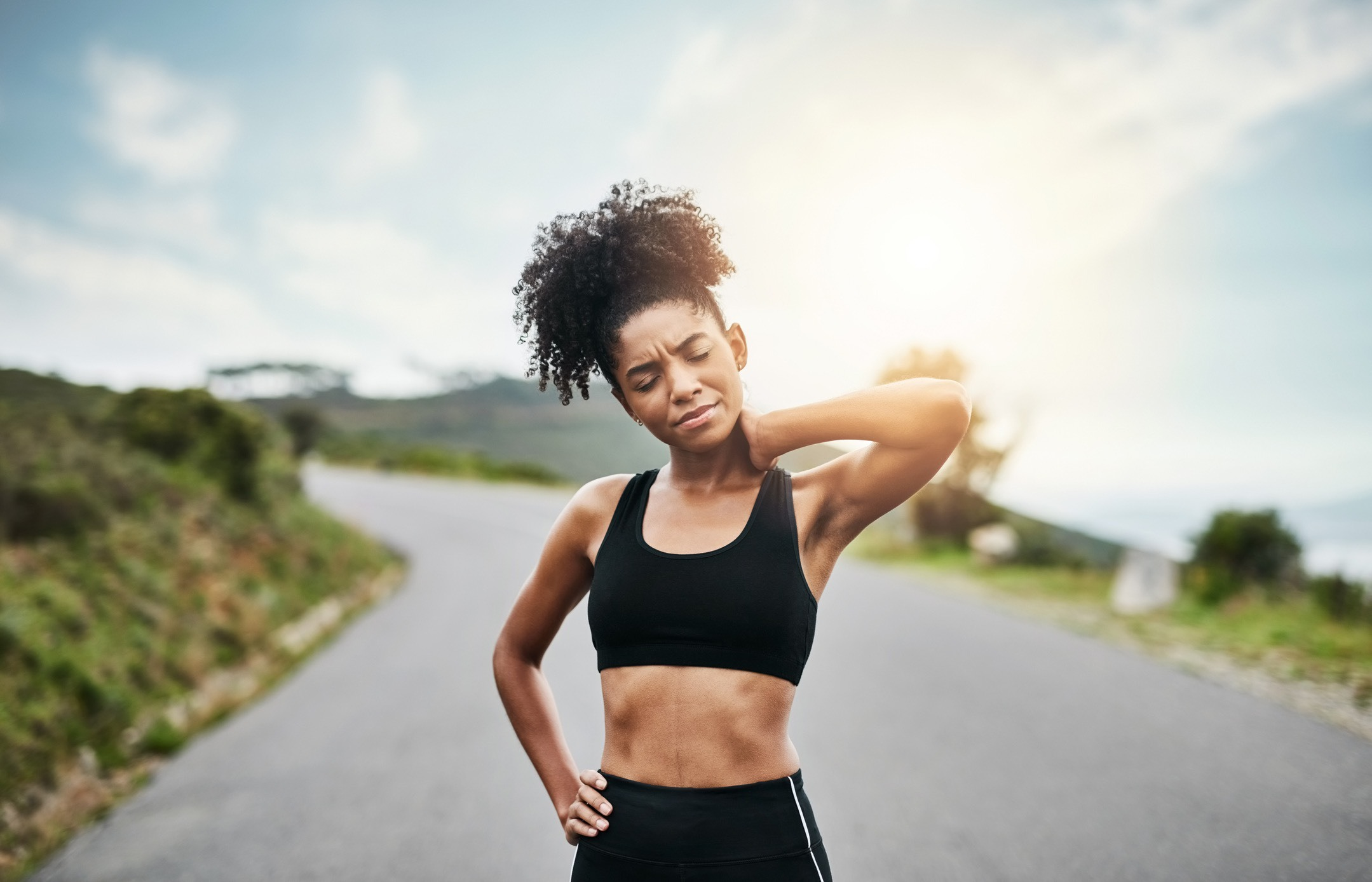 Woman on a run stopping to rub her neck