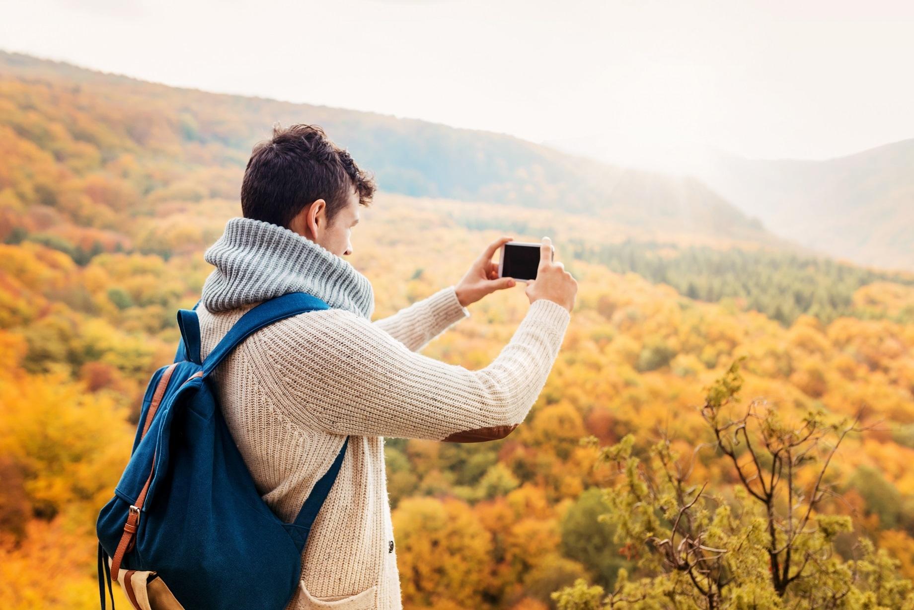 Man taking image of fall mountain scenery