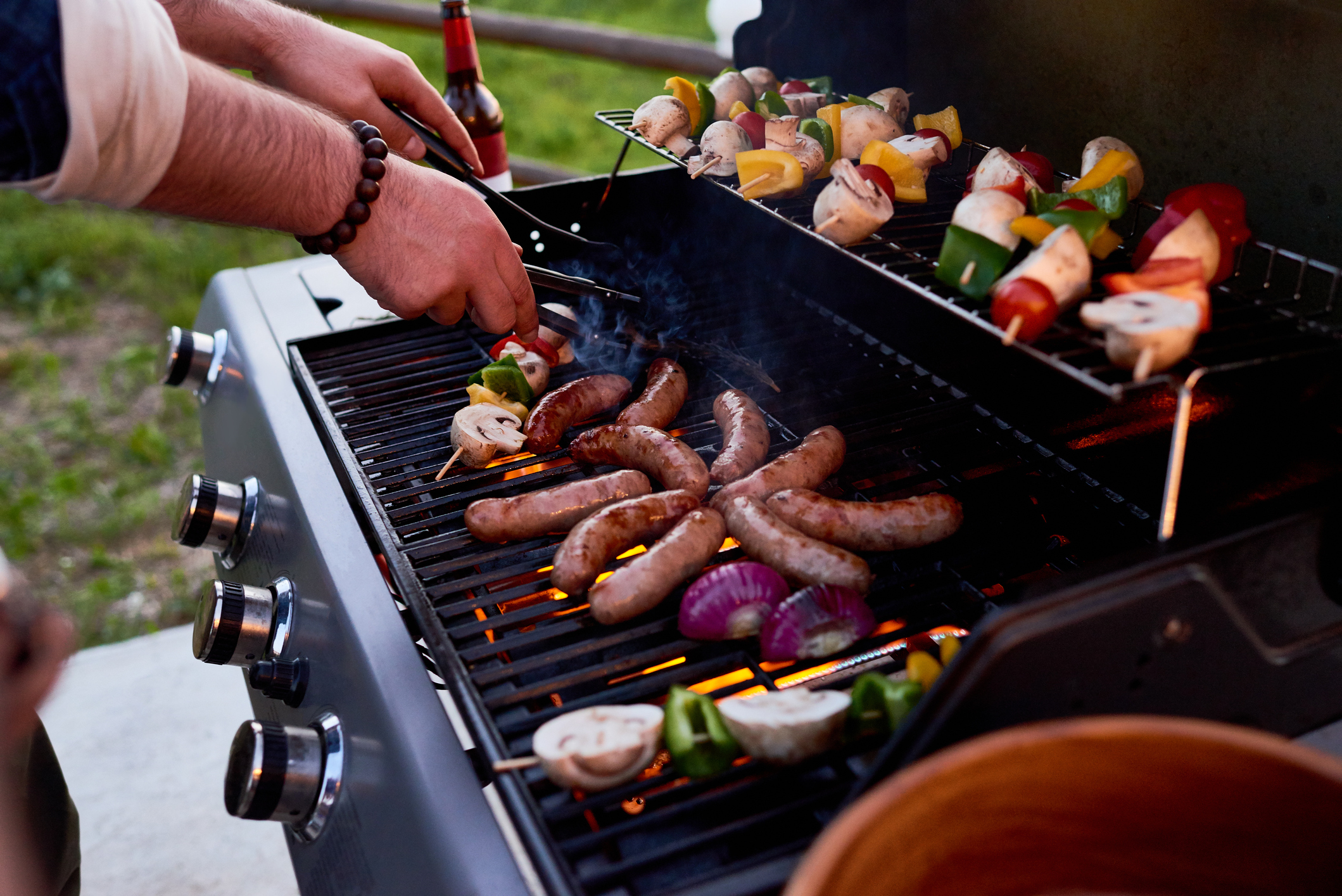 Meats and vegetables cooking on a grill