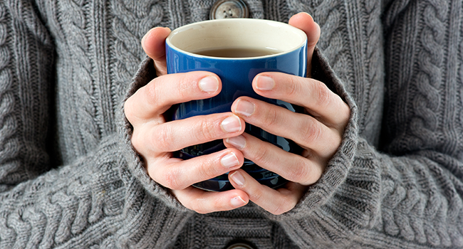 A person holding a filled mug